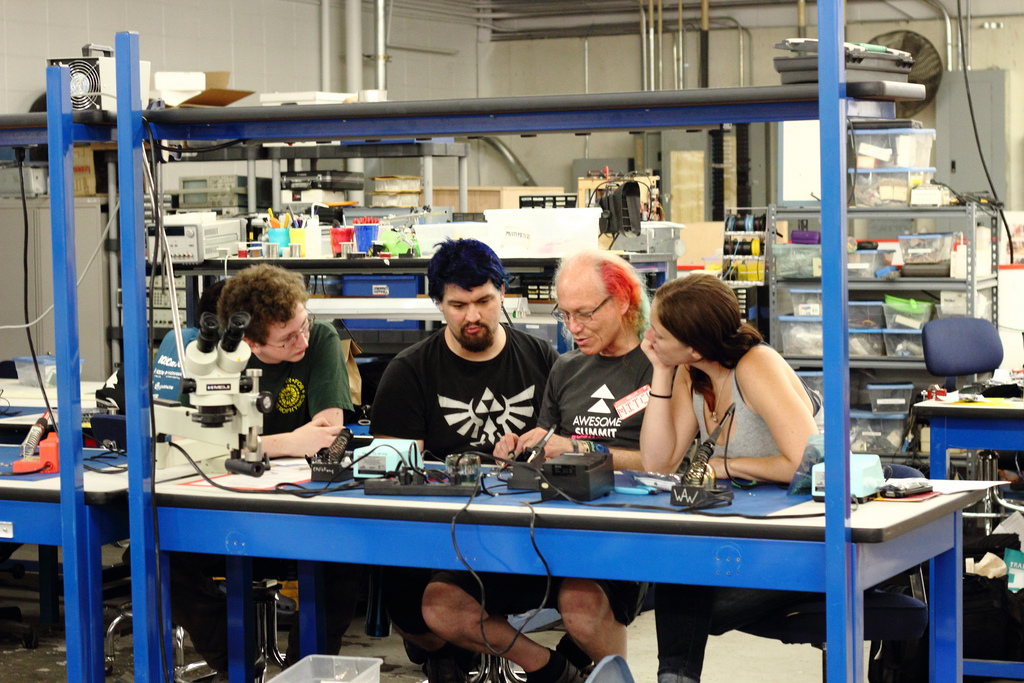 Group huddled over an electronics workbench